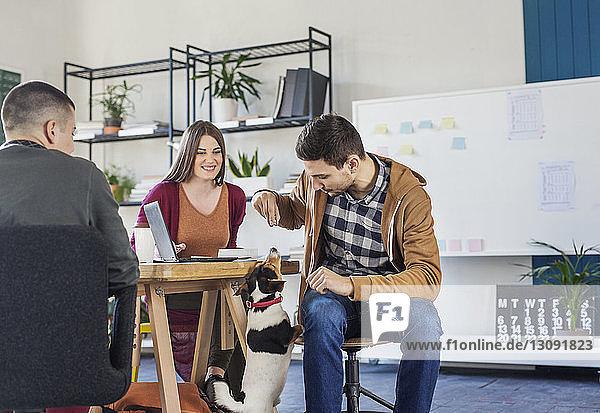 Frau betrachtet Mann beim Spielen mit Hund im Klassenzimmer