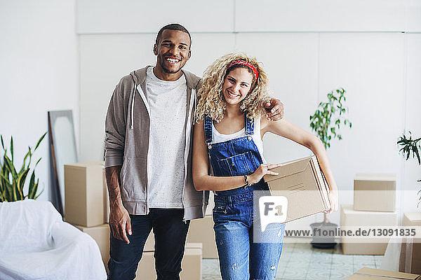 Porträt eines fröhlichen Paares am neuen Haus stehend