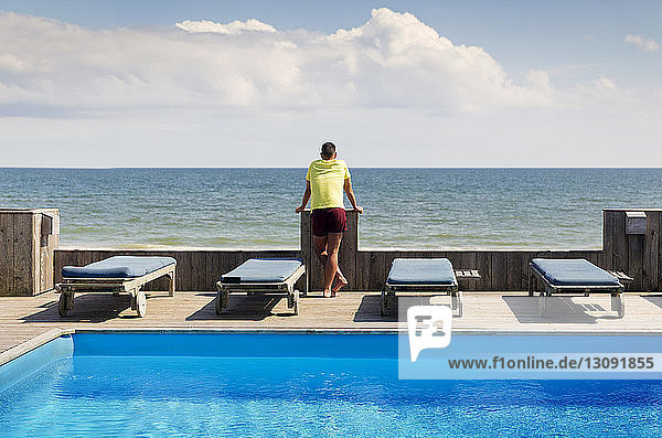Rear view of gay man standing by pool while looking at sea against sky