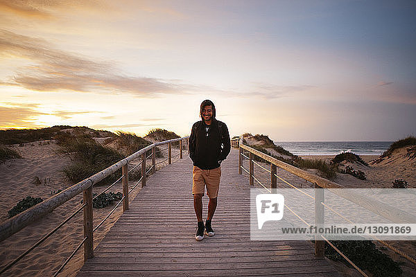Lächelnder Wanderer  der bei Sonnenuntergang auf einem Steg am Strand gegen den Himmel läuft