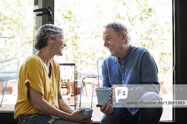 Fröhliches älteres Ehepaar unterhält sich  während es zu Hause Kaffeetassen am Fenster hält