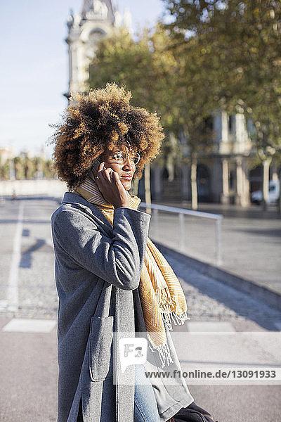 Frau spricht mit Mobiltelefon  während sie auf der Straße in der Stadt steht