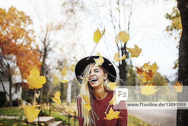 Glückliche Frau steht inmitten von fliegenden Herbstblättern