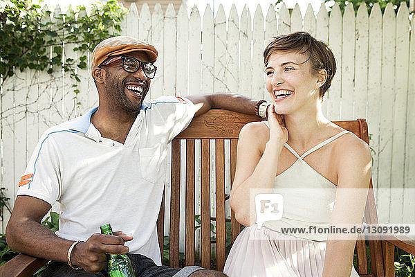 Glückliches Paar sitzt auf einem Stuhl im Rasen