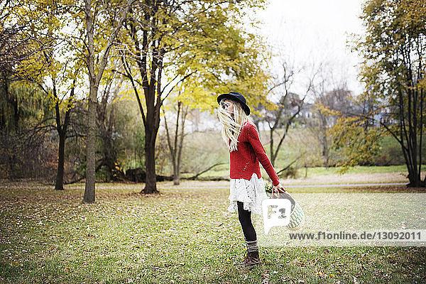 Seitenansicht einer Frau  die mit einer Einkaufstasche auf einem Grasfeld vor Bäumen steht