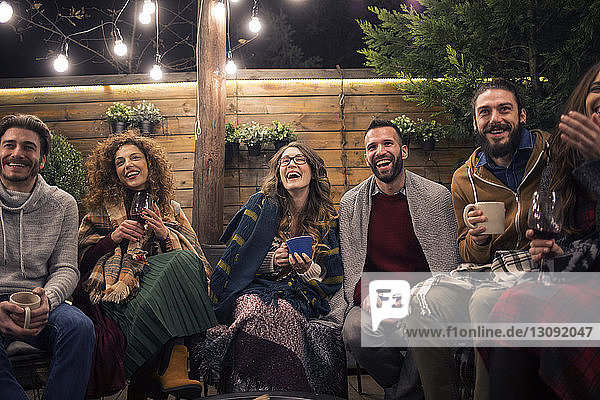 Cheerful friends with drinks in backyard at night