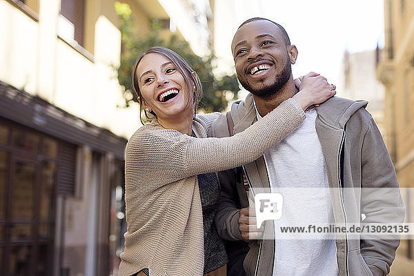 Happy woman embracing man while standing on city street