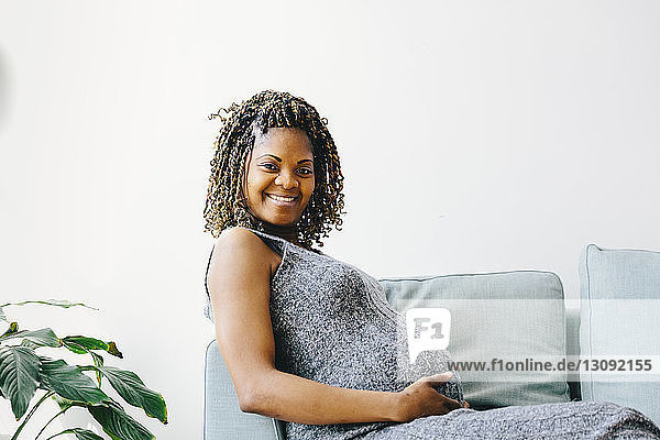 Porträt einer lächelnden schwangeren Frau  die zu Hause auf dem Sofa an der Wand sitzt