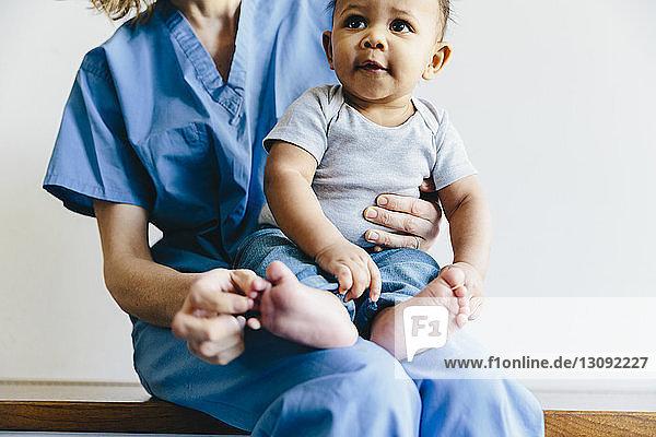 Mittelteil einer Ärztin  die einen süßen kleinen Jungen hält  während sie auf einer Bank vor weißem Hintergrund sitzt