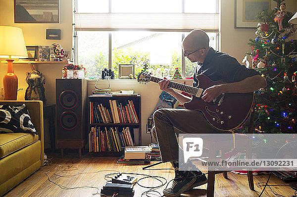 Mann spielt Gitarre  während er zu Hause auf einem Stuhl sitzt