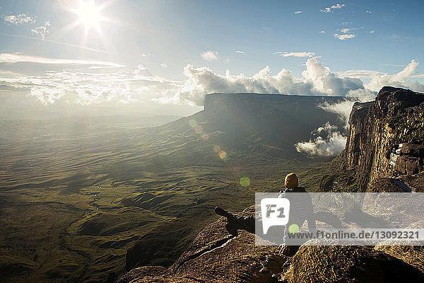 Rückansicht eines Mannes  der an einem sonnigen Tag auf einer Klippe sitzt