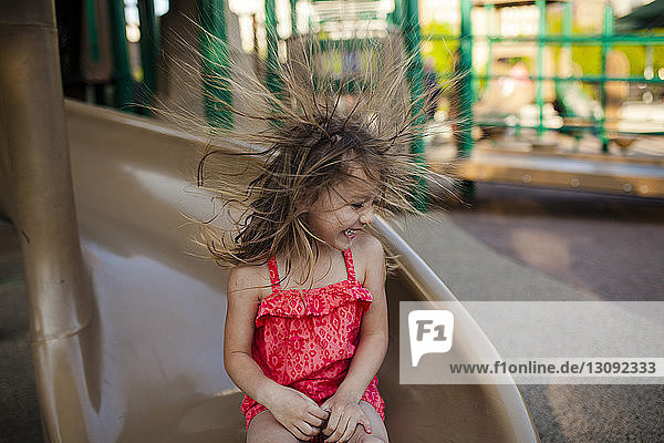 Happy girl playing flicking hair while sitting on slide