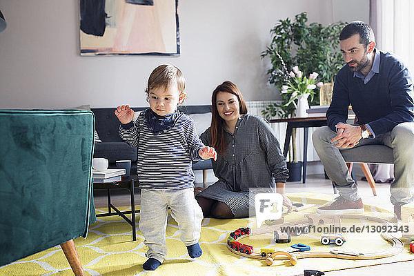 Glückliche Eltern,  die ihren Sohn im Wohnzimmer gehen sehen