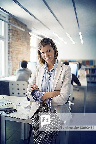 Porträt einer selbstbewussten Geschäftsfrau mit verschränkten Armen  die sich im Büro auf einen Tisch lehnt