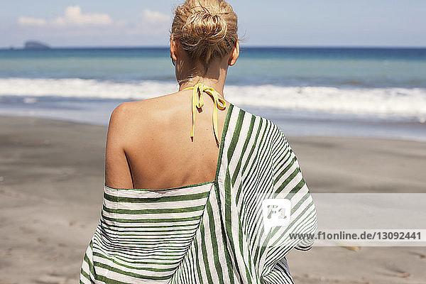 Rückansicht einer Frau  die am Strand spazieren geht
