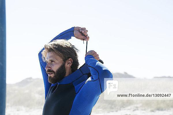 Mann trägt Badebekleidung am Strand gegen klaren Himmel am sonnigen Tag