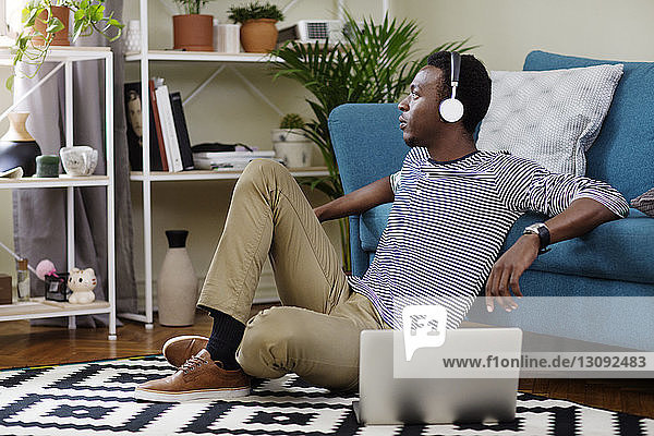 Thoughtful man listening music while sitting on floor in living room