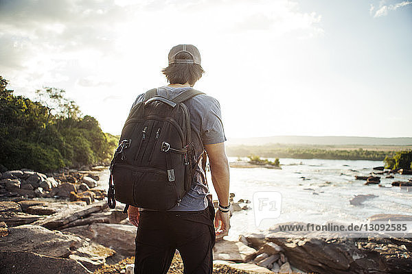 Rear view of hiker walking on rocky lakeshore