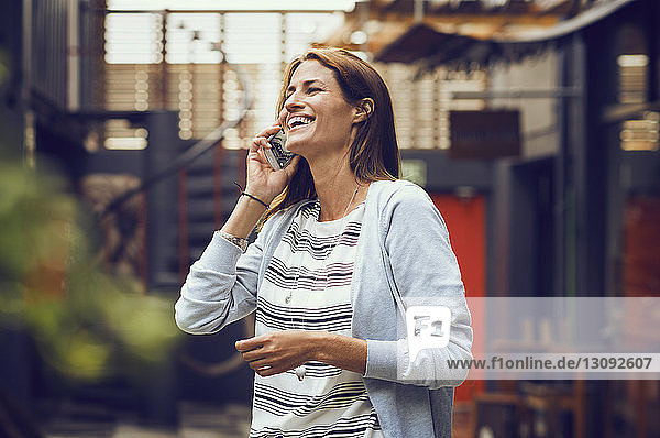 Cheerful woman answering smart phone outside cafe