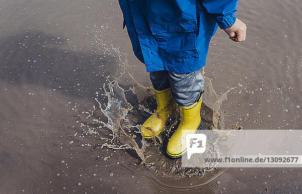 Low section of playful boy wearing yellow rubber boots while splashing puddle
