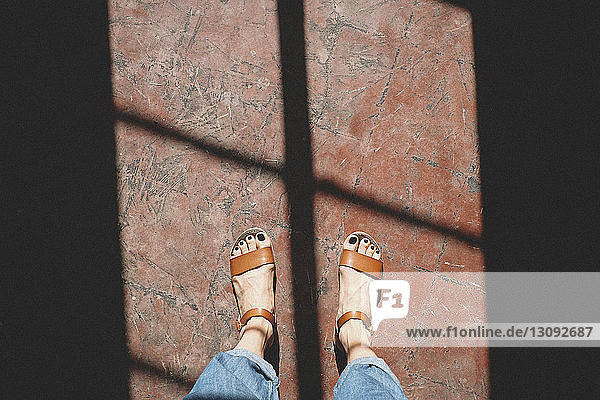 Low section of woman standing on floor in sunlight at darkroom