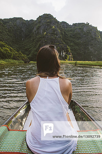 Rückansicht einer Frau  die in einem Boot auf einem Fluss reist