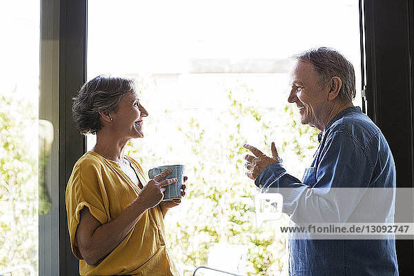 Side view of senior couple having coffee by window at home