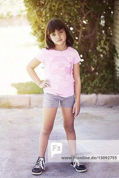 Porträt eines selbstbewussten Mädchens  das auf dem Boden gegen Bäume steht