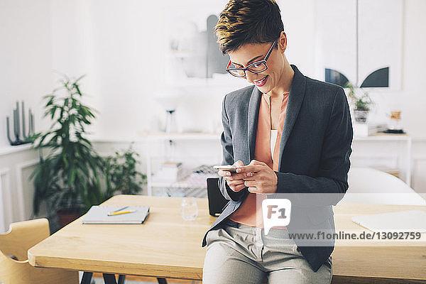 Glückliche Geschäftsfrau benutzt Mobiltelefon  während sie im Büro am Tisch steht