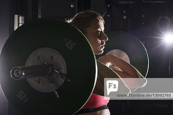 Determined woman lifting barbell in health club