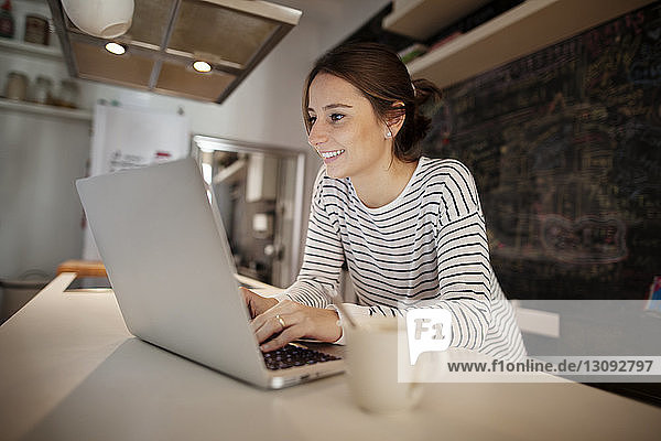 Happy woman working on laptop at table
