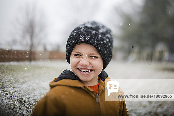 Porträt eines glücklichen Jungen  der im Winter auf dem Feld steht