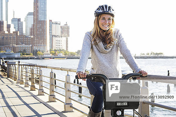 Smiling woman cycling on bridge by river in city during sunny day