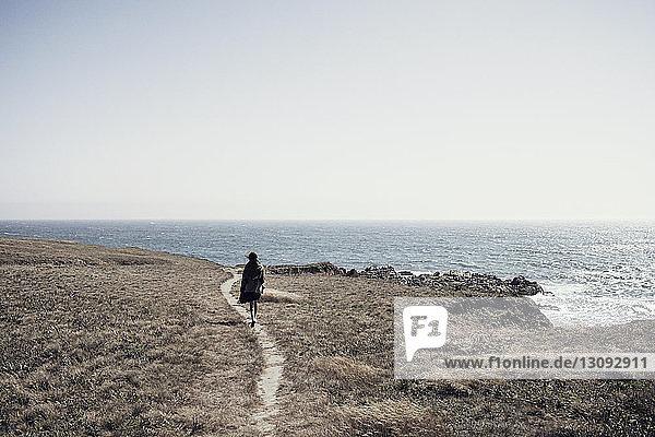 Frau geht auf Klippe am Meer gegen klaren Himmel