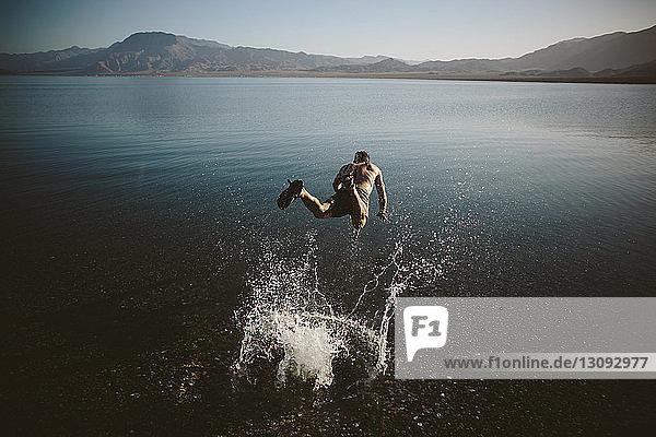 Hochwinkelaufnahme eines hemdlosen Mannes  der gegen Berge in den See springt