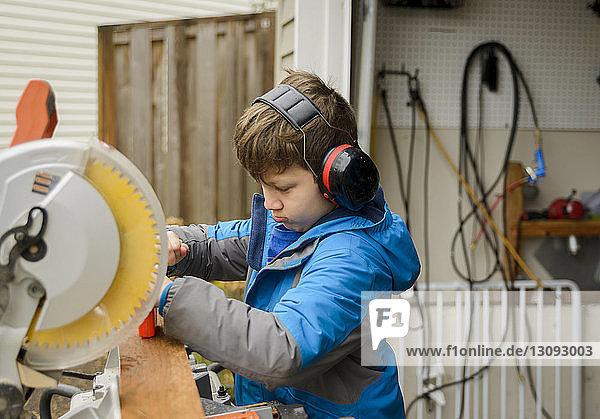Boy using ear protectors while working at backyard