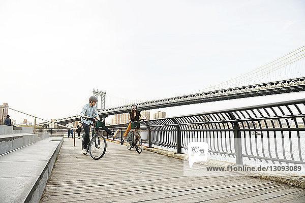 Couple enjoying while cycling on footpath by Manhattan bridge against sky