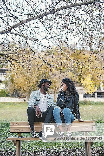 Romantisches Paar schaut sich an  während es im Park auf einer Bank gegen den Himmel sitzt