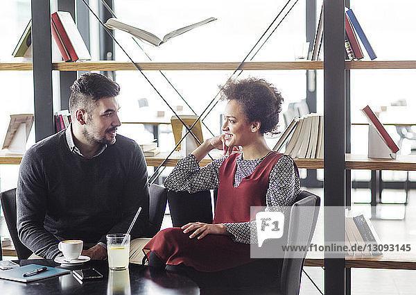 Geschäftsleute unterhalten sich  während sie am Tisch gegen ein Bücherregal im Restaurant sitzen