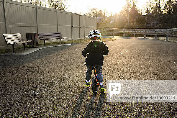 Rear view of boy wearing cycling helmet while riding bicycle on road during sunset