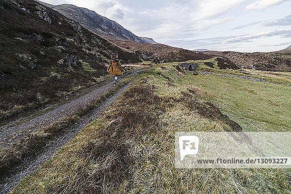 Rückansicht einer Frau  die auf einem Wanderweg inmitten von Feld und Bergen geht