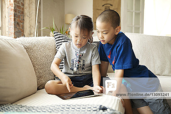 Siblings using tablet computer while sitting on sofa in living room