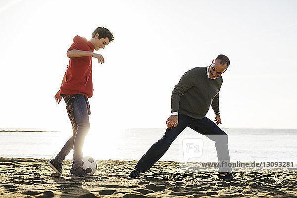 Vater und Sohn spielen bei strahlendem Sonnenschein am Strand bei klarem Himmel Fussball
