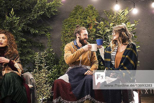 Lächelnde Freunde stoßen auf Getränke an  während sie nachts im Hinterhof sitzen