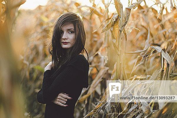 Porträt einer jungen Frau  die inmitten von Feldfrüchten auf dem Feld steht
