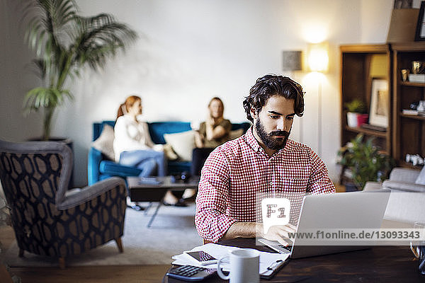Businessman working on laptop while sitting at table in creative office