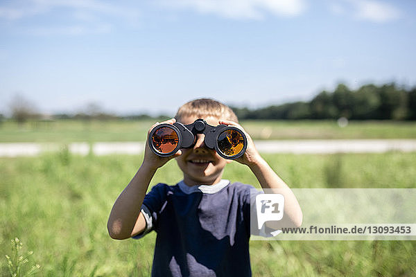 Playful boy looking through binoculars while standing on field during sunny day