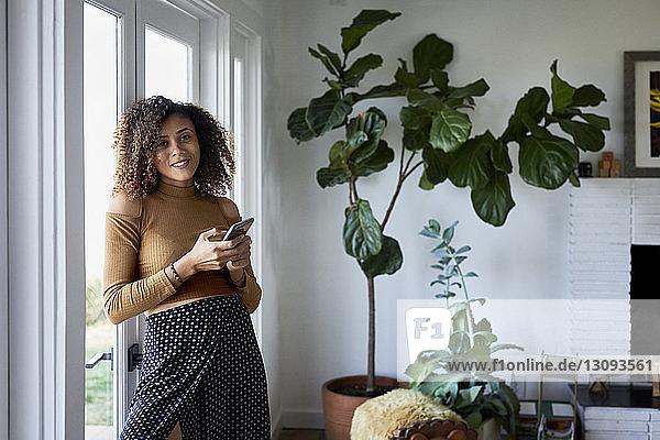 Porträt einer lächelnden Frau  die ein Mobiltelefon benutzt  während sie zu Hause am Fenster steht