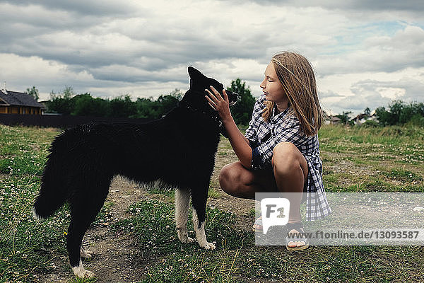 Teenage girl petting dog while crouching on field against stormy clouds