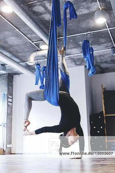 Junge Frau  die in voller Länge Luftyoga praktiziert  während sie im Fitnessstudio an der Hängematte hängt